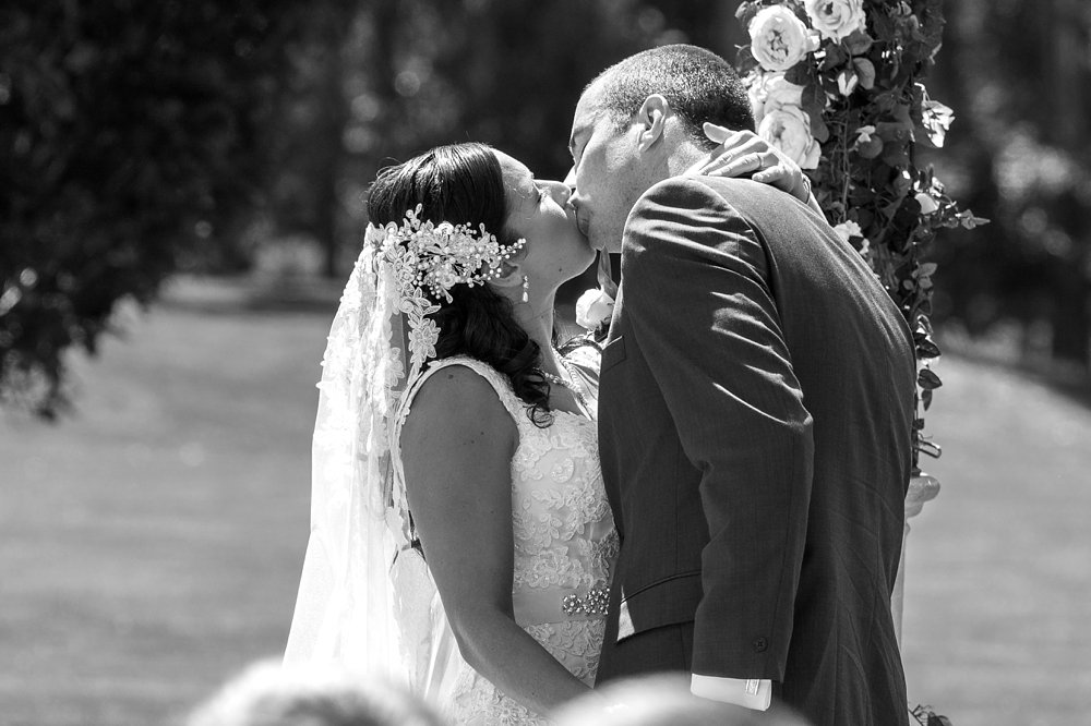 bride and groom having first kiss photo at Rosemount Estate Wedding Venue in Ohoka