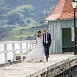 Akaroa wedding photographer with the bride and groom at the harbour