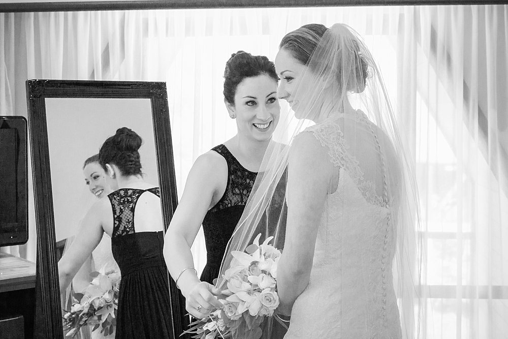 Melton Estate Wedding-Sister and Maid of honour helps the bride put on her veil