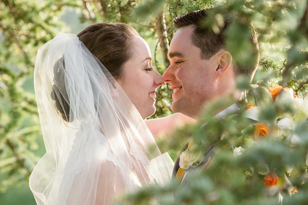 close up of Bride and groom captured through foliage by Christchurch Wedding Photographer