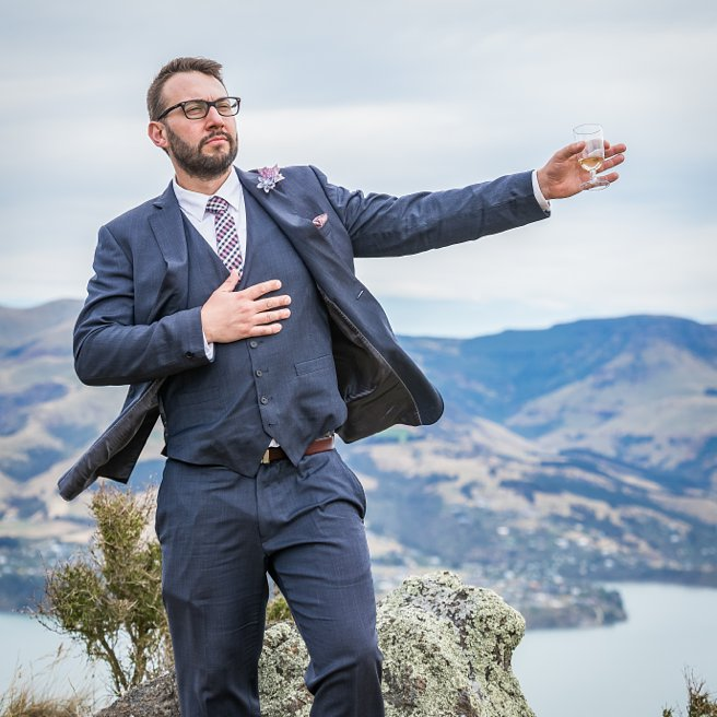 groomsman feeling proud while at the top of a hill while holding a wine glass tin one out stretched hand with other hand on his chest