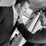 Wedding photo of the best man fixing the groom's pocket square