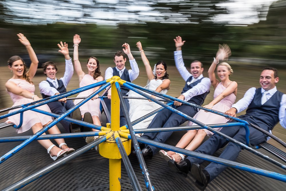 wedding photo of bridal party on merry-go-round in a Christchurch park