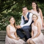 groom poses for a photograph with the bridesmaids