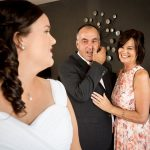 Photo of the bride with her emotional parents in the back ground
