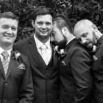 Photograph of groomsmen being affectionate by leaning on each others shoulder