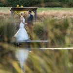 NZ Wedding Photographer photo of bride and groom stand holding hands and looking at each other shot through long grass across a pond