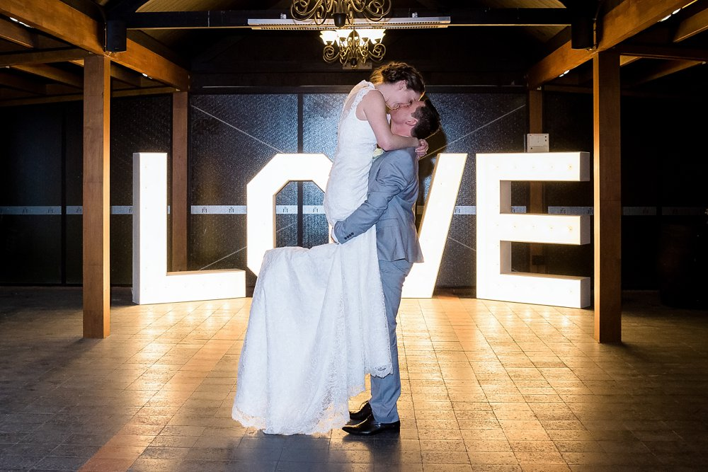 groom lifting-kissing bride on dance floor-Wedding Photographers Christchurch