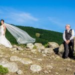 Christchurch wedding photographer capture of the bride and groom up on top of a hill with the bride's veil being caught in the wind
