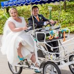 Hanmer wedding photographer image of bride and groom having fun riding a two seater bike on there wedding day