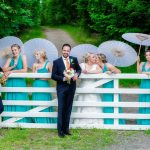 wedding photography of the bridal party standing in front of a white wooden farm gate