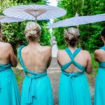 Wedding photography of bridesmaids stating in line with back to the photographer and bride in the distance