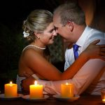 Bride and groom sitting by a table at night lit by candles on the table