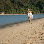 bare footed bride running away from groom on the beach