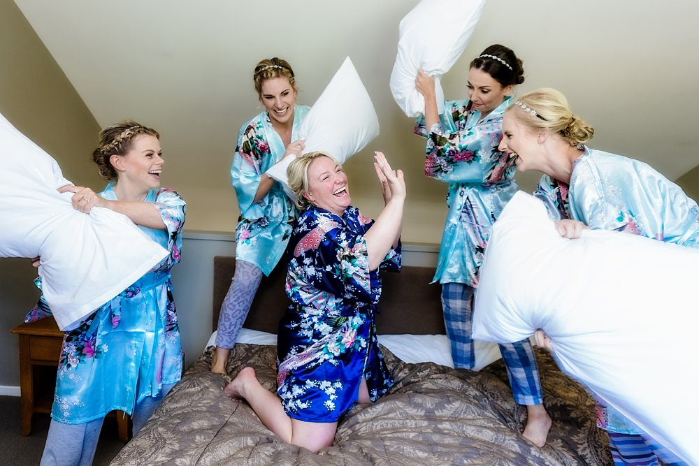 bride and bridesmaids have pillow fight at the heritage hotel in hanmer springs