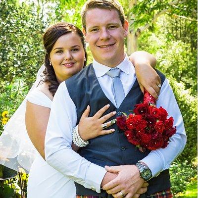 bride holding arms over grooms shoulders at Flaxmere Gardens Wedding Venue in Hawarden in Canterbury