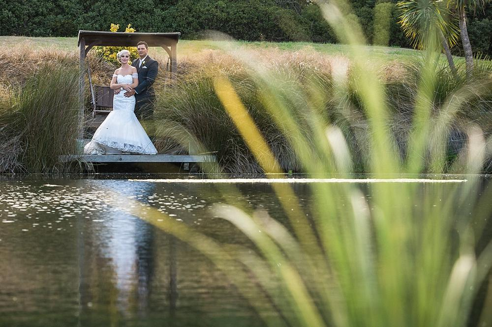 Bride and groom standing across a pond at Flaxton Manor B&B, photo by Wedding Photographers Christchurch Pip and Oz