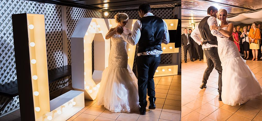 Bride and groom dancing in front of an illuminated Love sign at Bramble Grove Wedding Venue