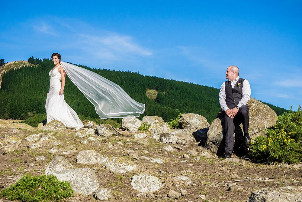 Bride and groom on a hilltop on a windy day with veil playing in the wind and groom looking at bride outside Cossars Wineshed Wedding venue