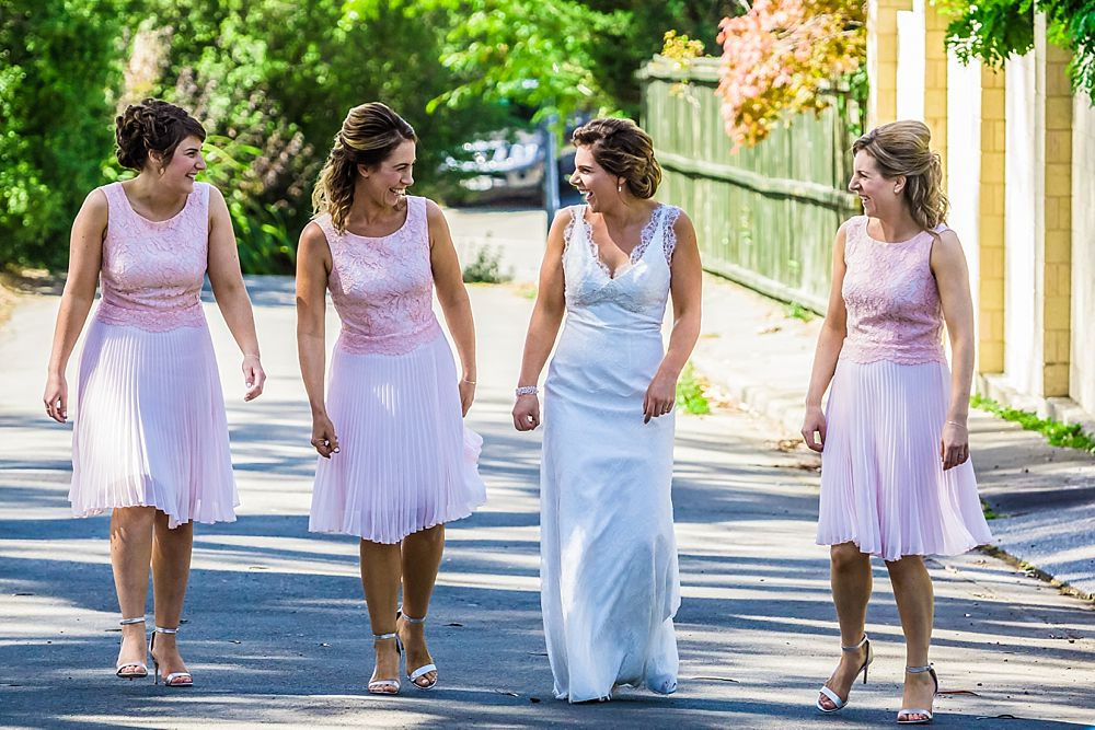 Bridesmaids walking down the street outside bride's home in Christchurch