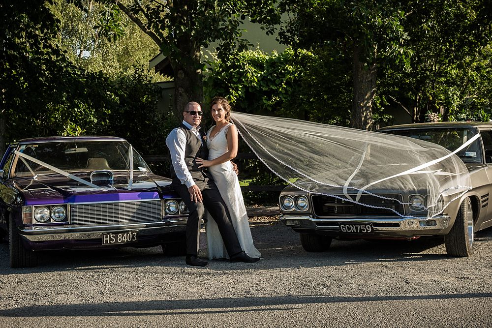 Bride and groom standing between two cars at the wedding venue