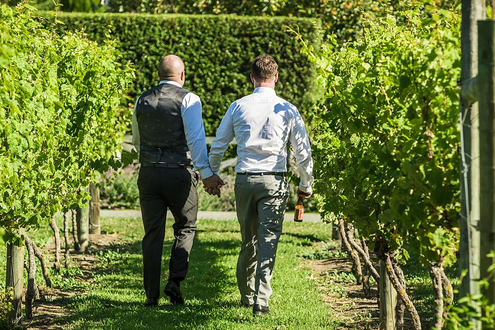 Groom and groomsman walk hand in hand in the vines at Cossars Wineshed Wedding Venue captured by Christchurch wedding photographer Oz