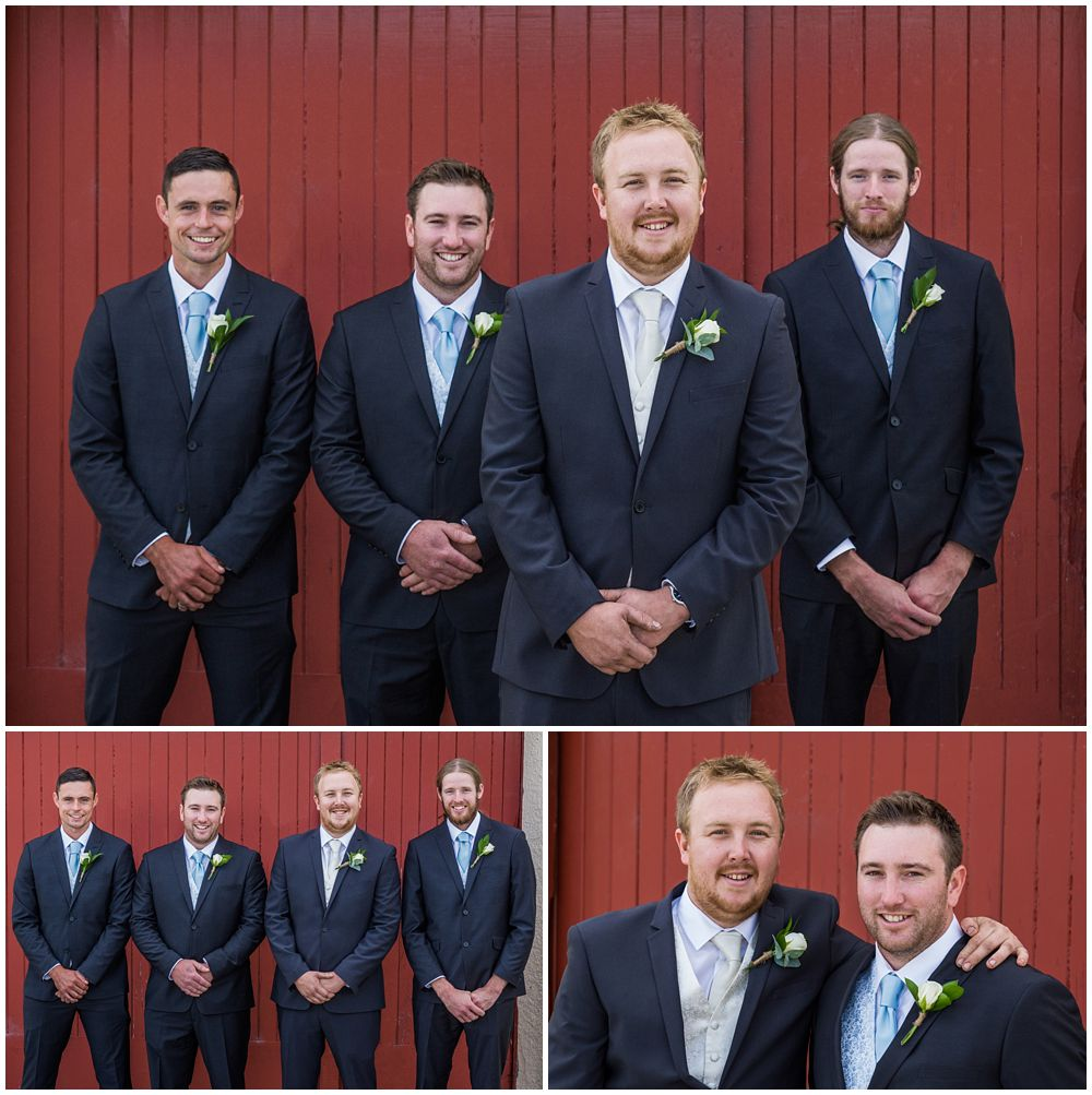 Groom and groomsmen pose for photos in front of red wooden door