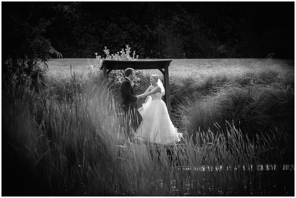 Bride and Groom standing across pond at Flaxton Manor