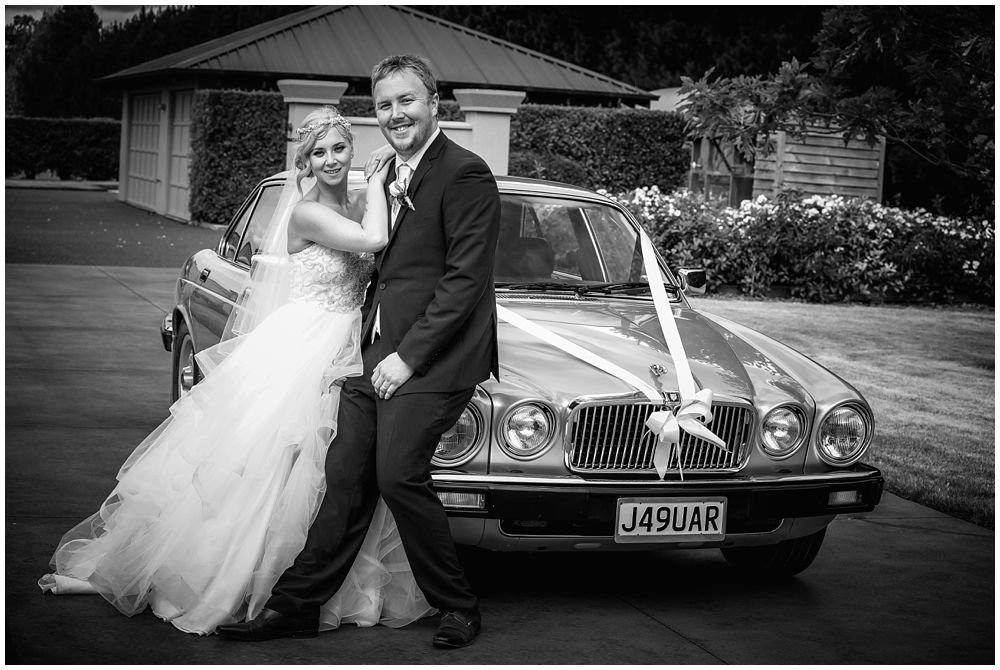 Groom and bride leaning on the bridal car at Fixation Manor