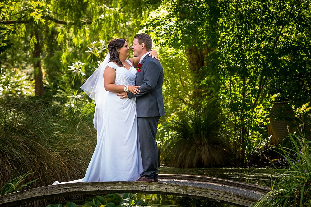 Bride and groom on a pond bridge at Flaxmere Garden Wedding Venue
