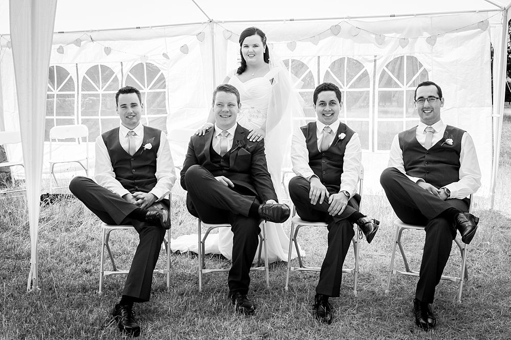 Groom and groomsmen pose for a photo while siting on chairs with bride standing behind the groom