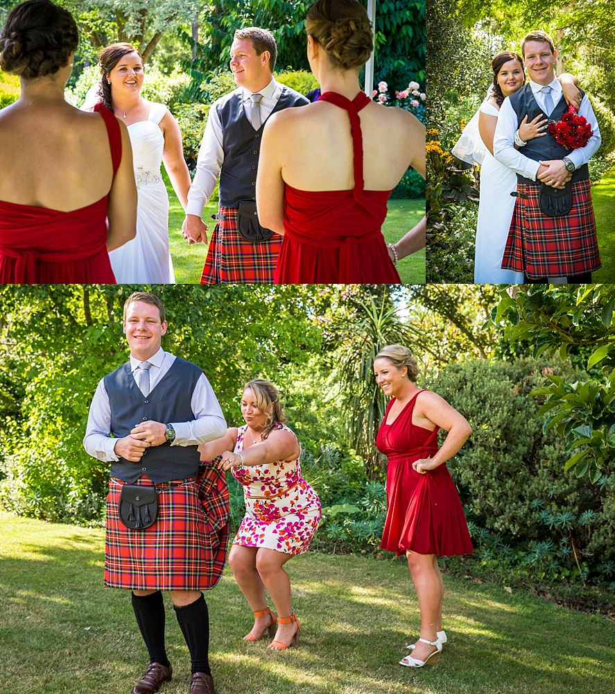 Groom in a red and black kilt with his sisters at wedding venue
