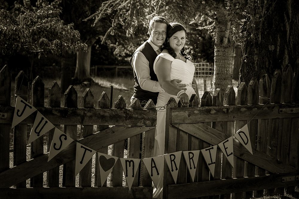 bride and groom by a farm gate at Flaxmere Garden Wedding Venue in North Canterbury
