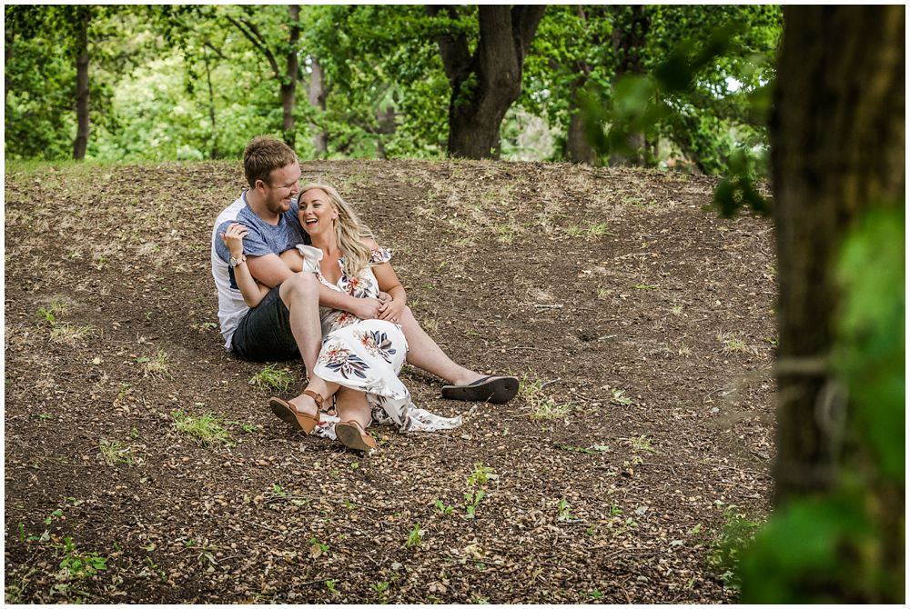 Kaiapoi domain engagement photography with couple sitting on the ground