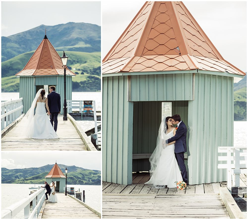 Bride and groom posing in front of a hut on wharf at Akaroa Harbour