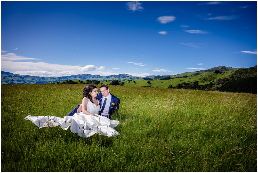 Mt Vernon Lodge Wedding-Bride and groom sitting in the green grass-Akaroa