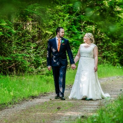 Pip and Oz capture a photo of bride and groom walking along a forest path, in Hanmer Springs