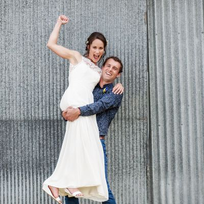 bride and groom celebrating marriage bride fist pumping groom lifting bride at Hampton Lea Gardens