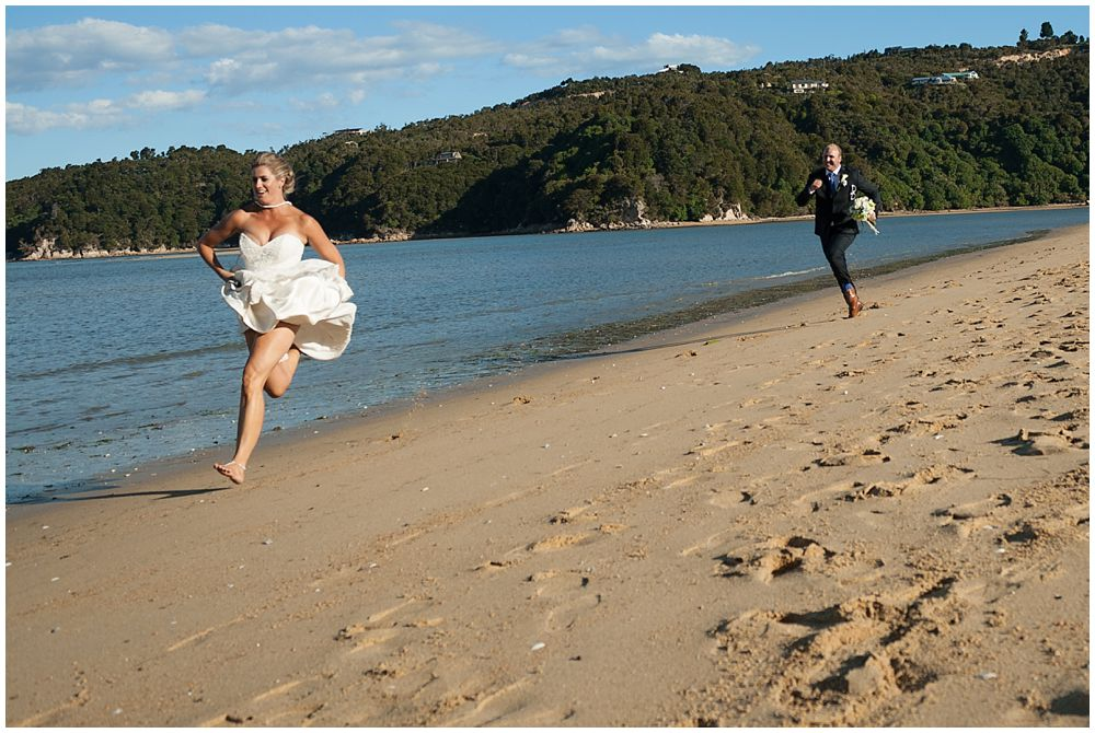Christchurch Wedding Photographer's photo-bride running from groom at beach