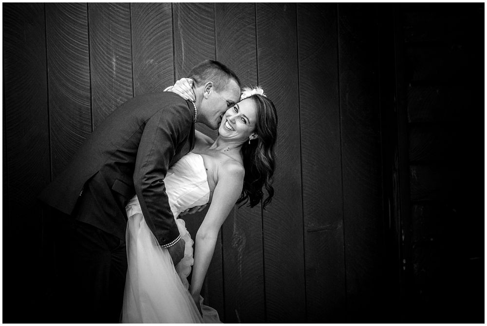 Bride-groom kissing infant of barn door