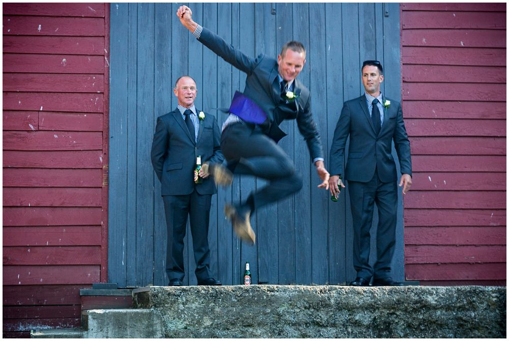 groom jumping from top of stairs at Tipapa Woolshed Barn Wedding Venue
