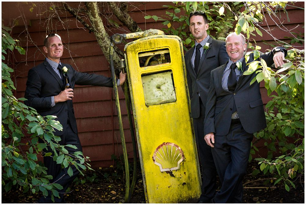 Groom-groomsmen standing by vintage petrol pump at Tipapa Woolshed