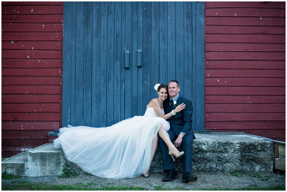 bride-groom sitting infant of barn at Tipapa Woolshed Barn Wedding Venue