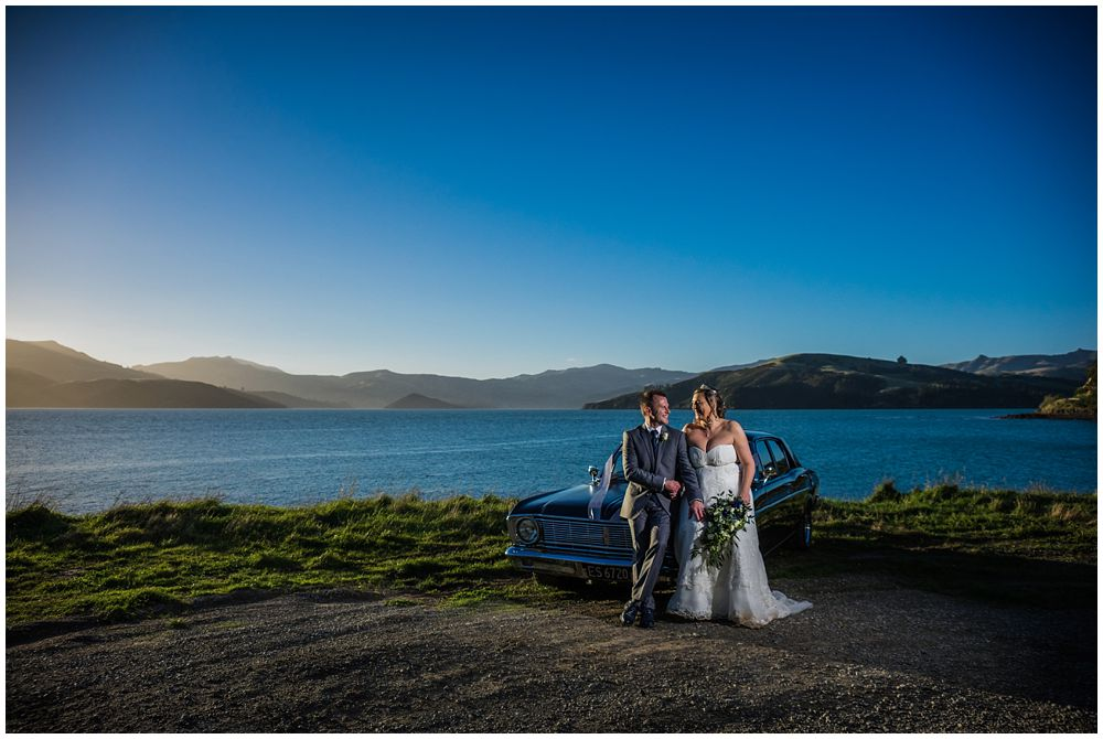 bride and groom with car and sea vista