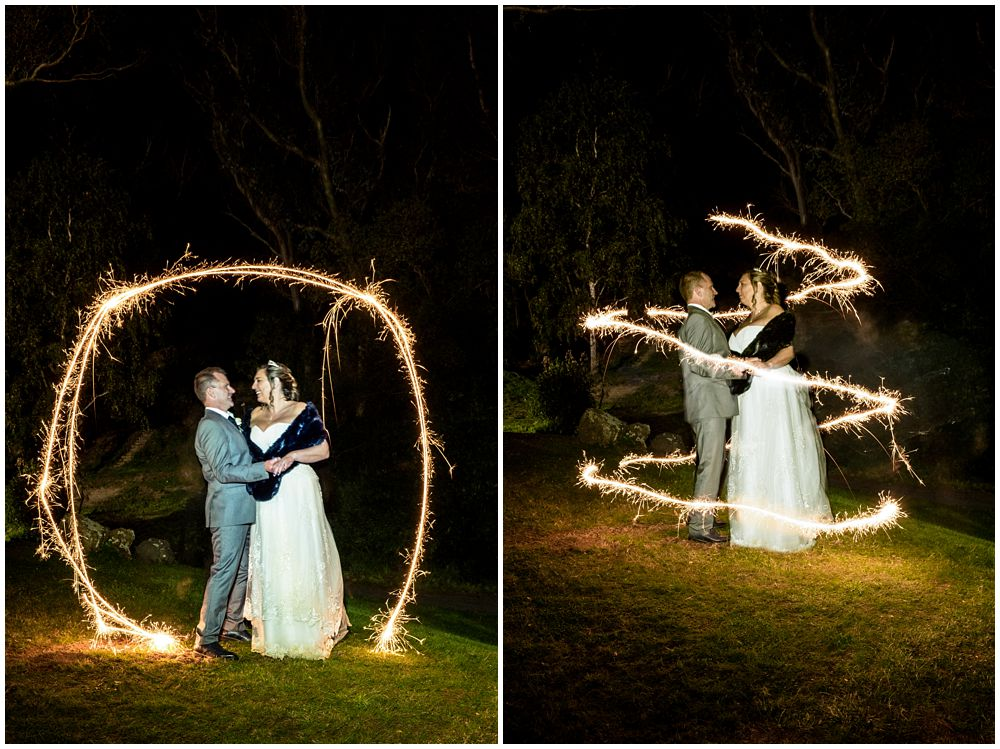 bride and groom pose for sparkler photo