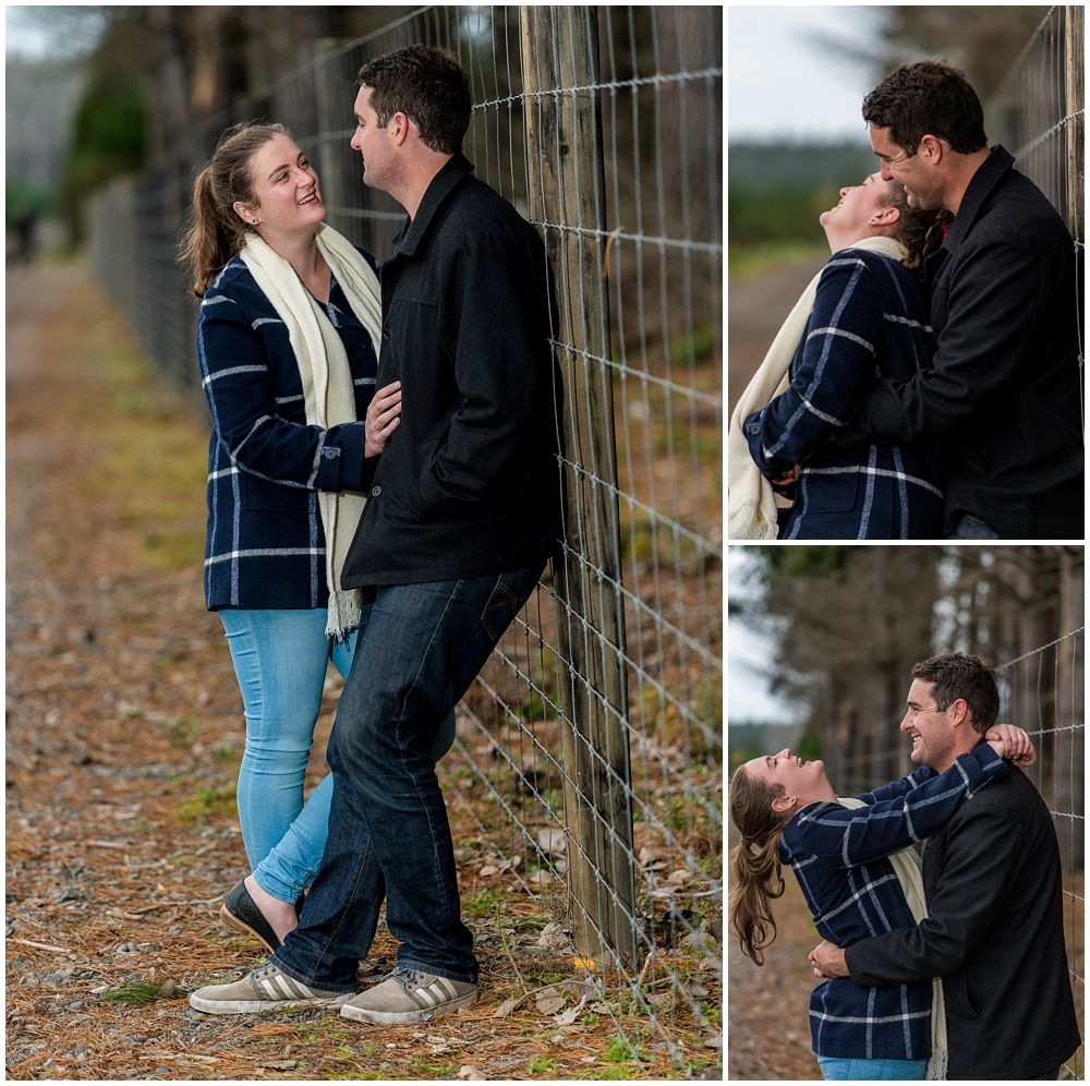 engaged couple standing by the fence