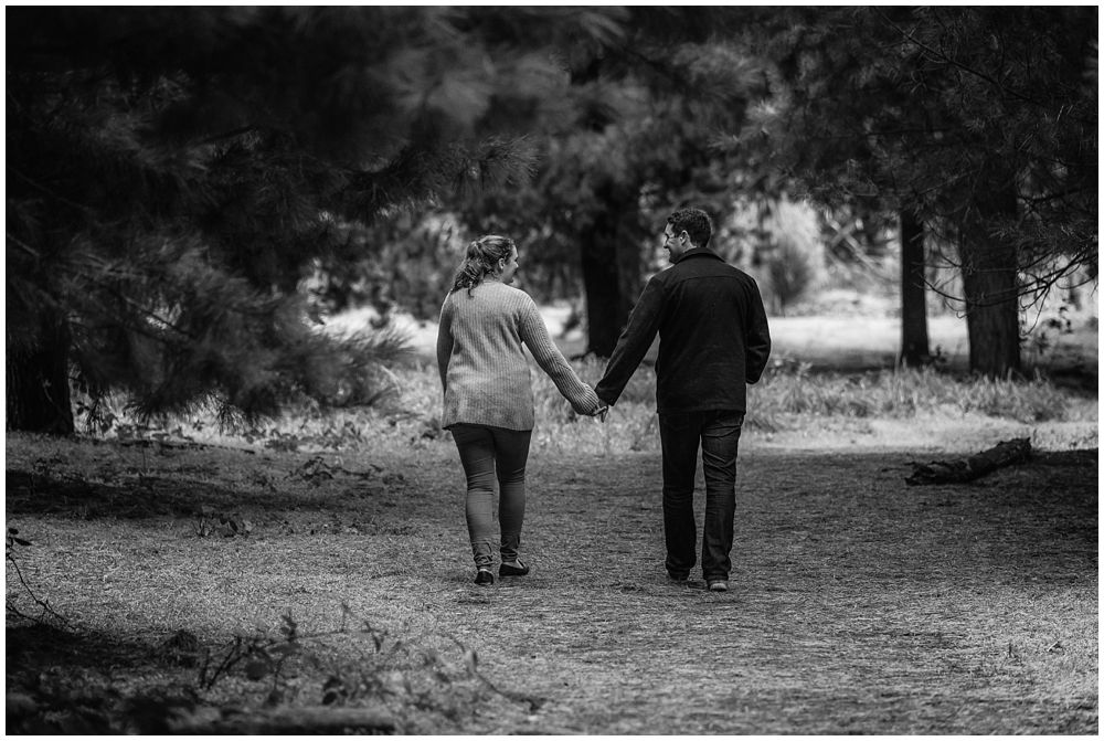Lovers walking hand in hand in forest