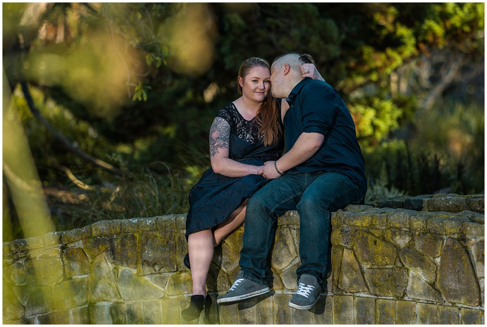 Christchurch Botanic Gardens Autumn Engagement Photography Couple sitting and kissing on bridge