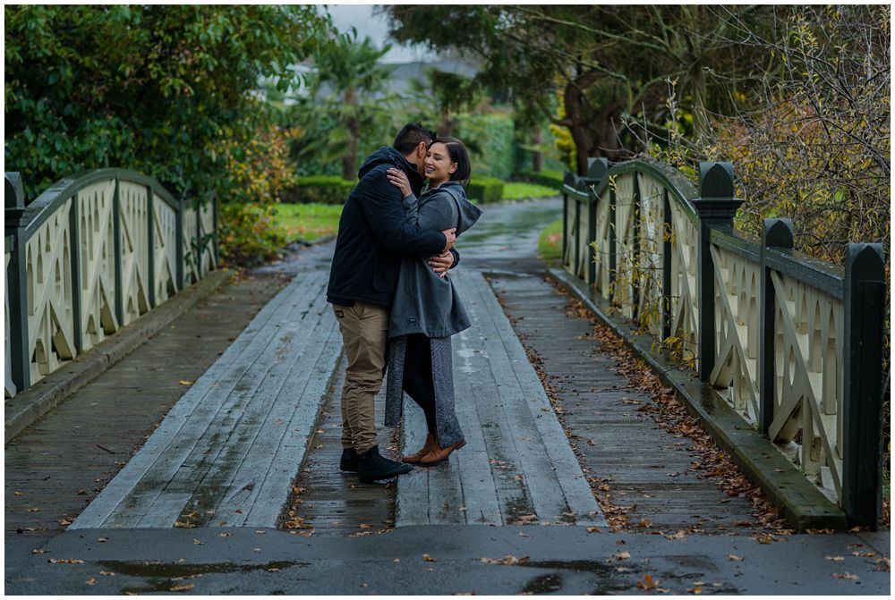 engaged couple standing on a bridge at Mona Vale Gardens