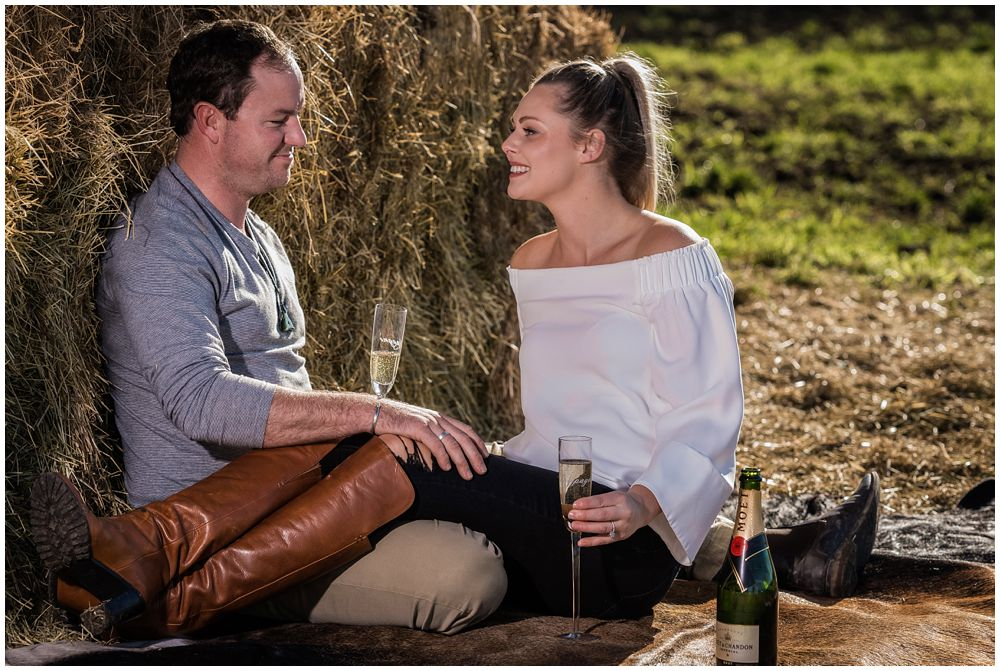 engaged couple sitting on cow hide and drinking wine